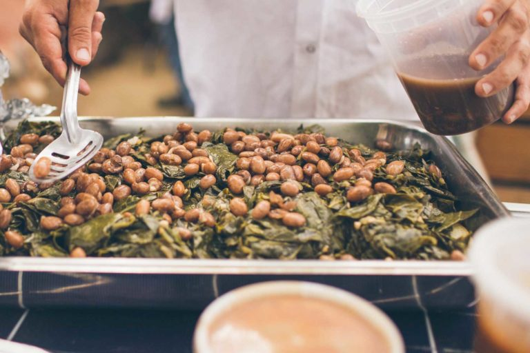 Braised Collard Greens with cranberry beans being scooped by a chef.
