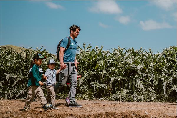 Parent and children walking through farm fields.