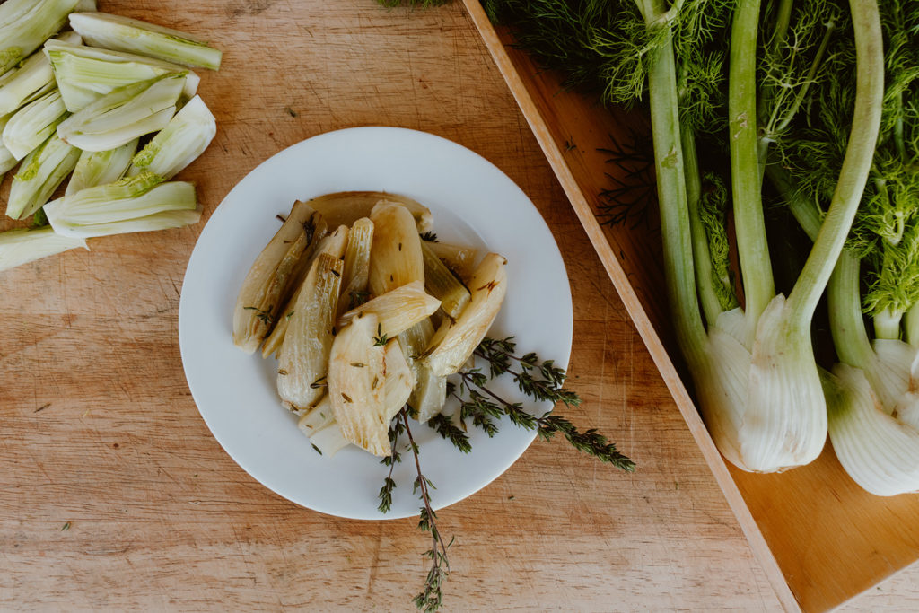 Plate of braised fennel next to fresh fennel.