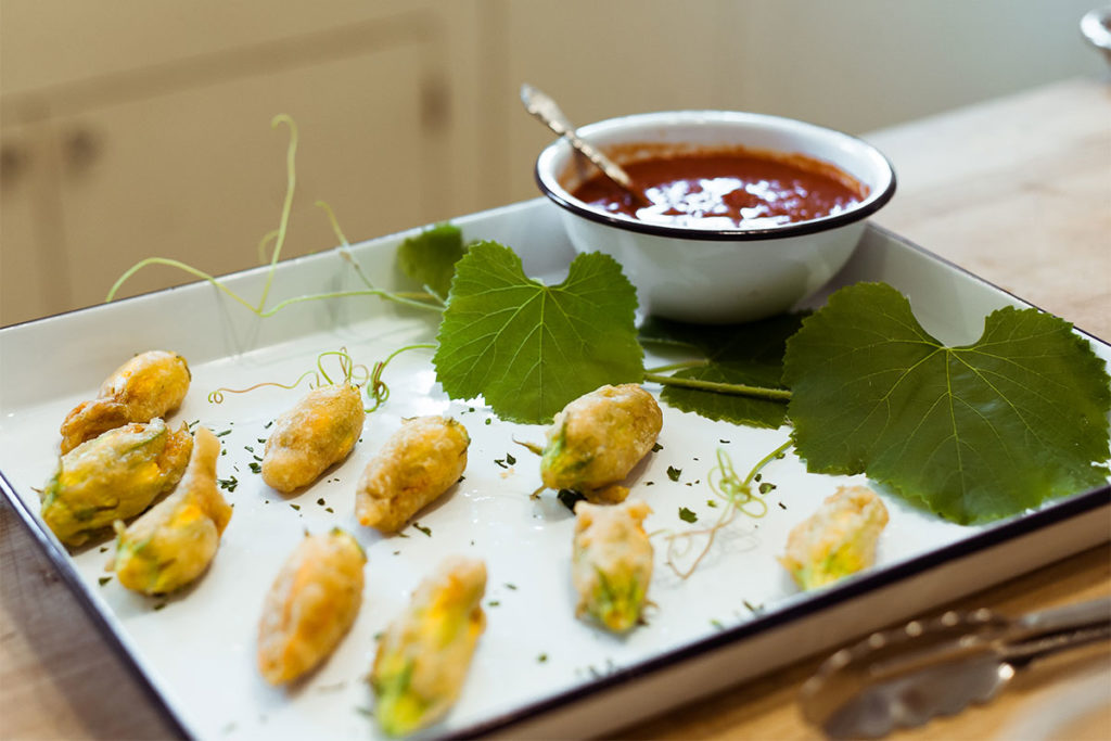 Stuffed Tempura Squash Blossoms on a platter with dipping sauce.