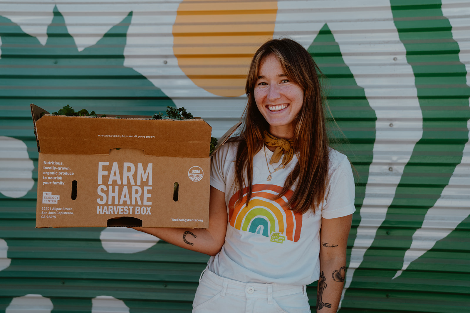 Woman holding box of fresh organic produce
