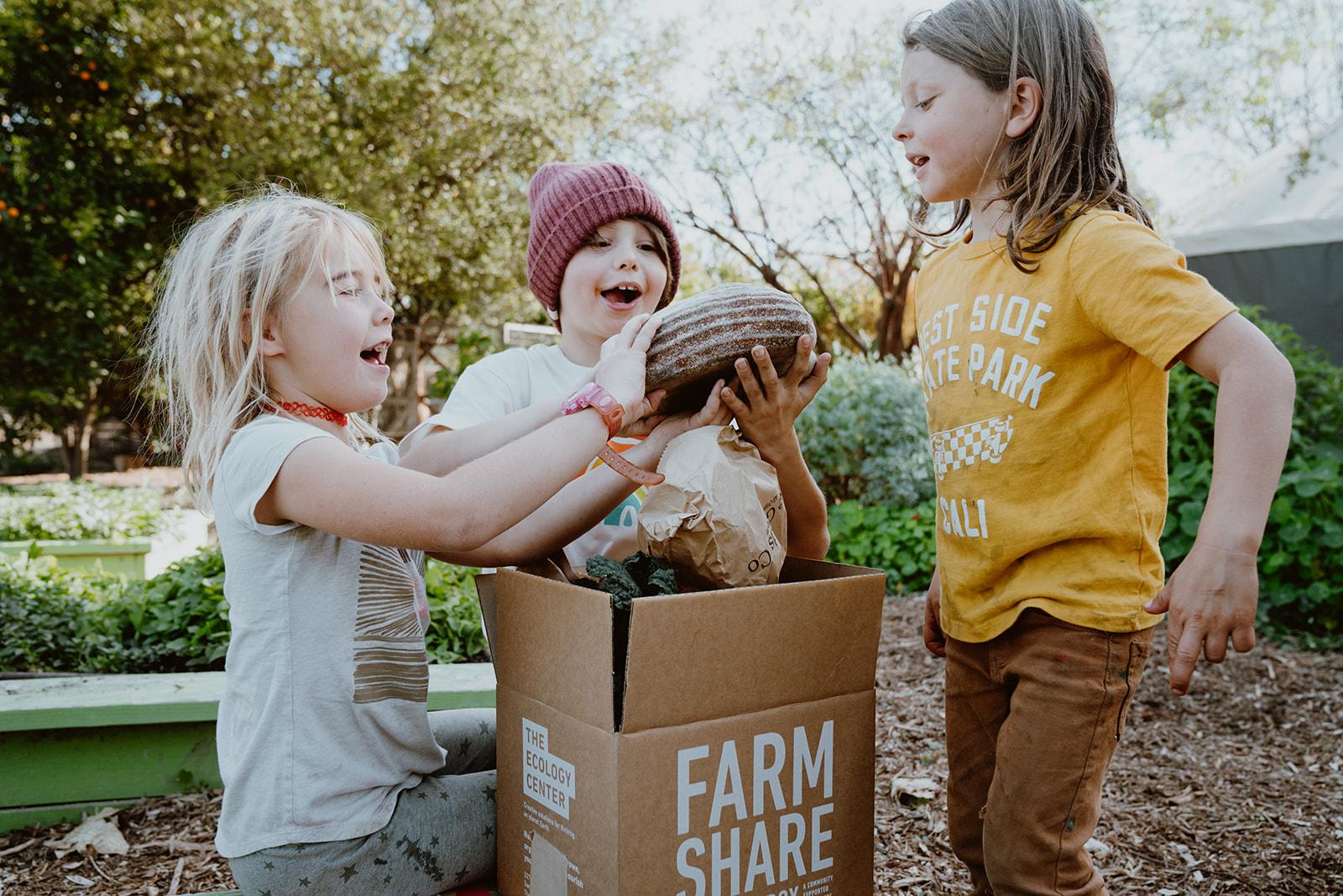 Children opening field kit to find bread inside.