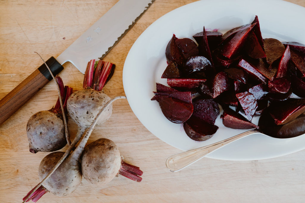 Beets plated next to raw beets on cutting board.