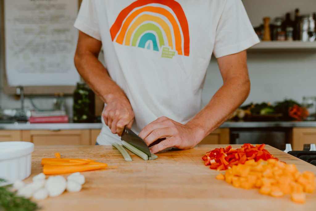 Celery stalk being chopped on cutting board alongside carrots and bell peppers.