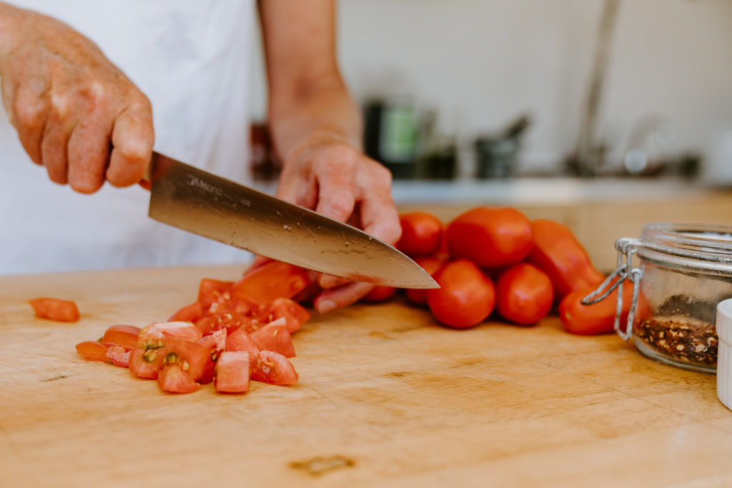 San Marzano tomatoes getting diced with sharp blade.