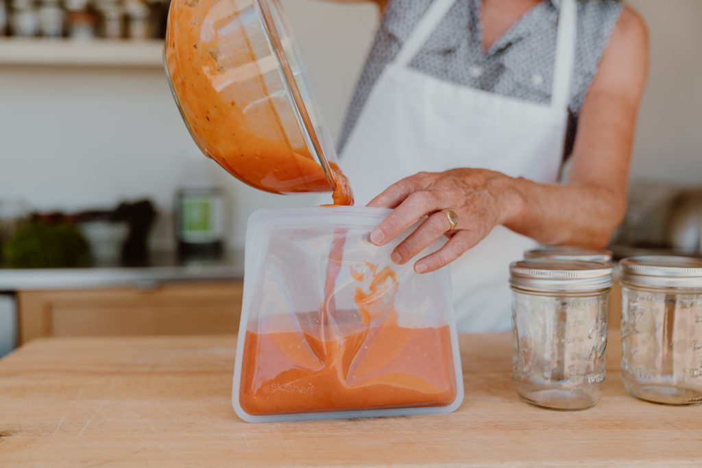 Marinara for pizza sauce being poured into clear Stasher reusable bag.