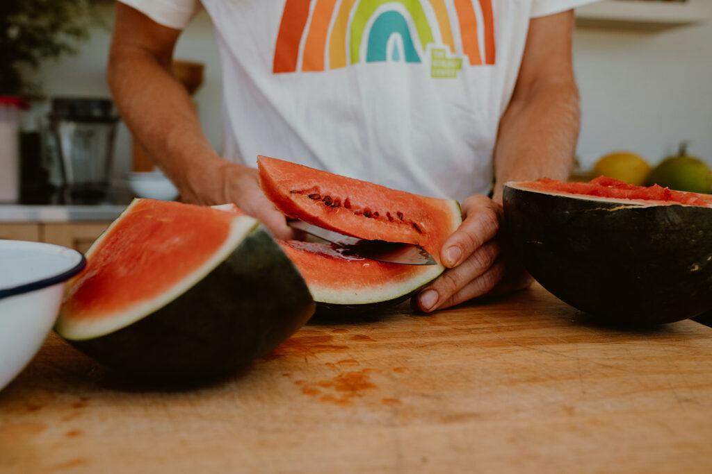 Sugar baby watermelon being sliced with sharp blade.