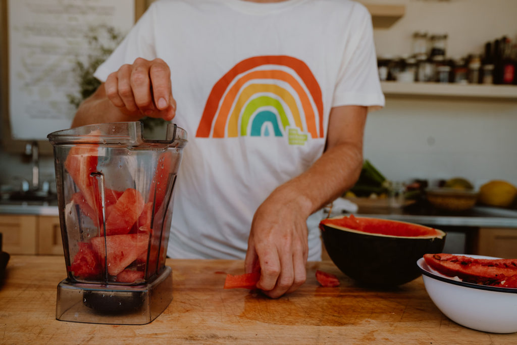 Watermelon pieces being placed into blender.