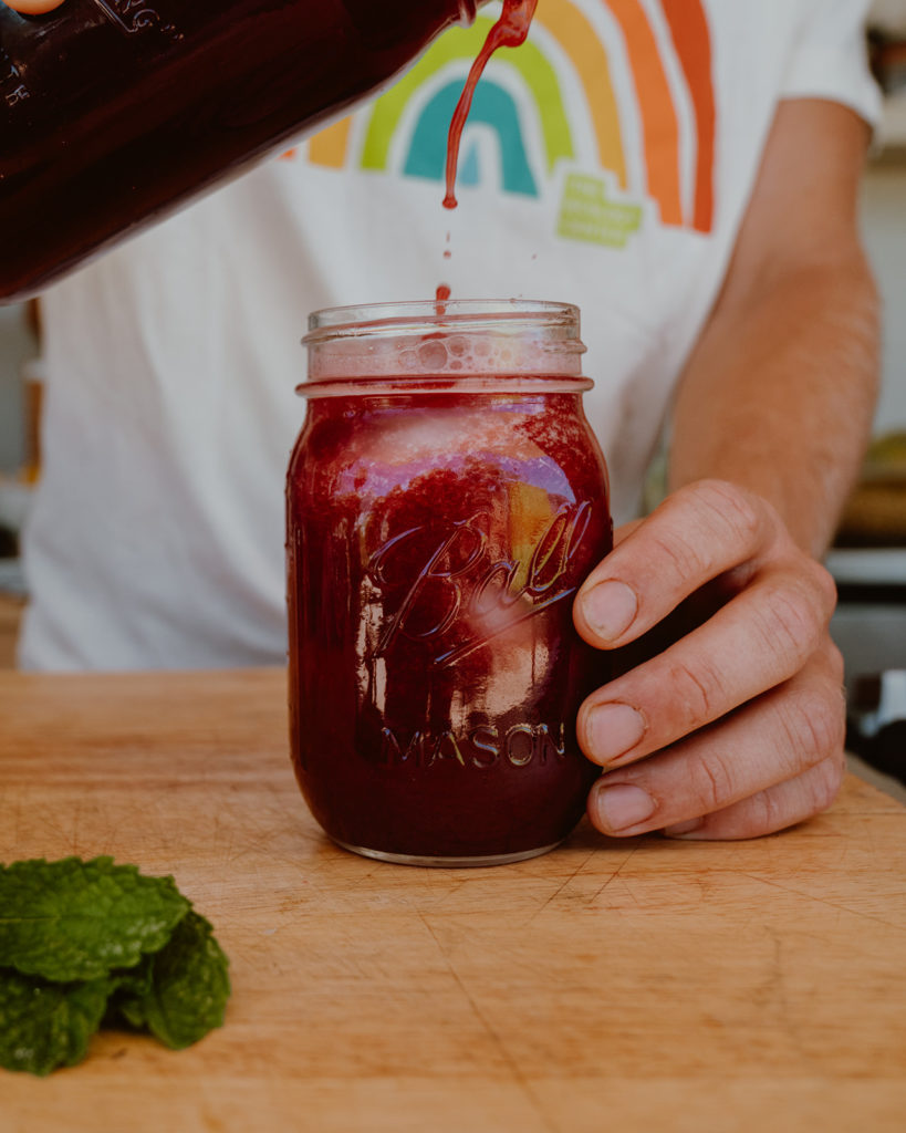 Watermelon and Hibiscus Agua Fresca being poured into mason jar.