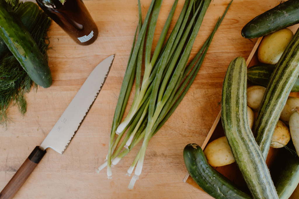 Aerial view of knife, scallions, and cucumbers on cutting board.