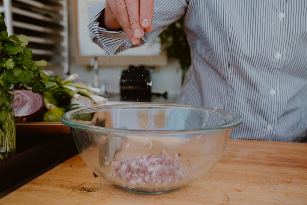 Minced red onions in bowl being sprinkled with a pinch of salt.