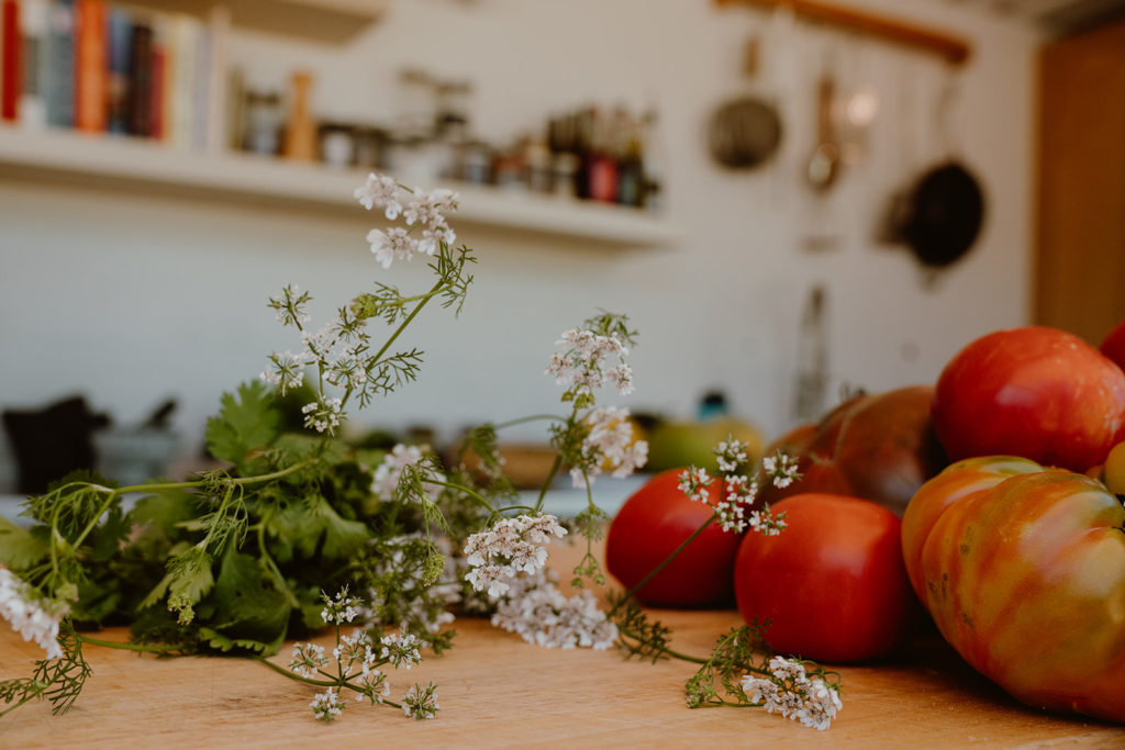 Flowering cilantro and variety of tomatoes on top of cutting board.