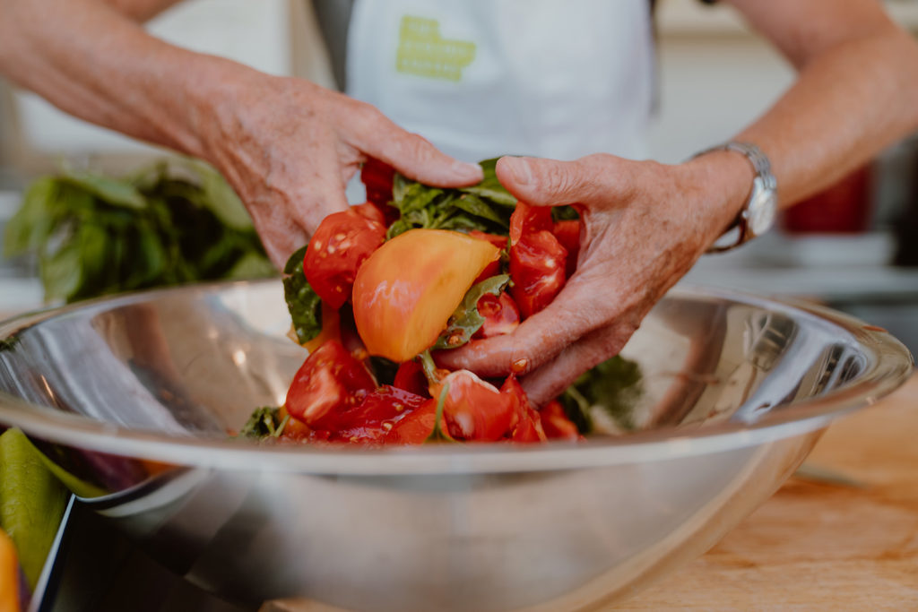 Quartered tomatoes, crushed garlic, and basil being mixed with hands in a bowl.