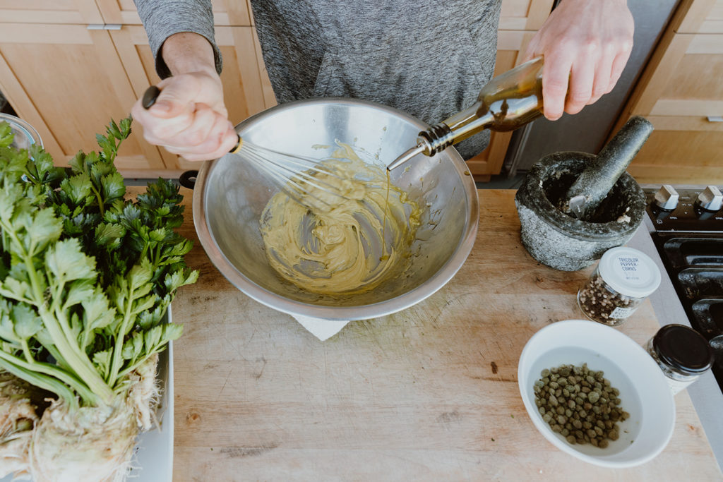Mixing aioli dressing while adding olive oil.