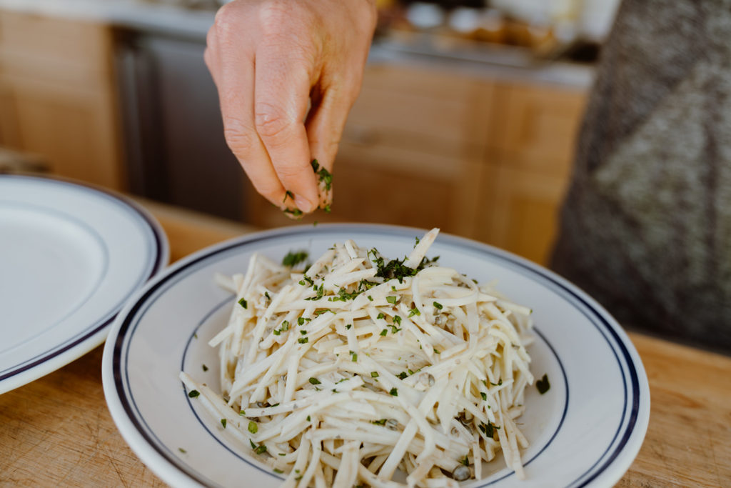 Sprinkling fresh parsley over the celery root remoulade.