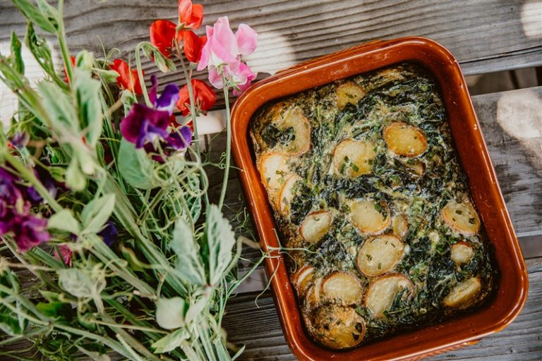 Kale and potato frittata in ceramic dish next to fresh flower boquet.