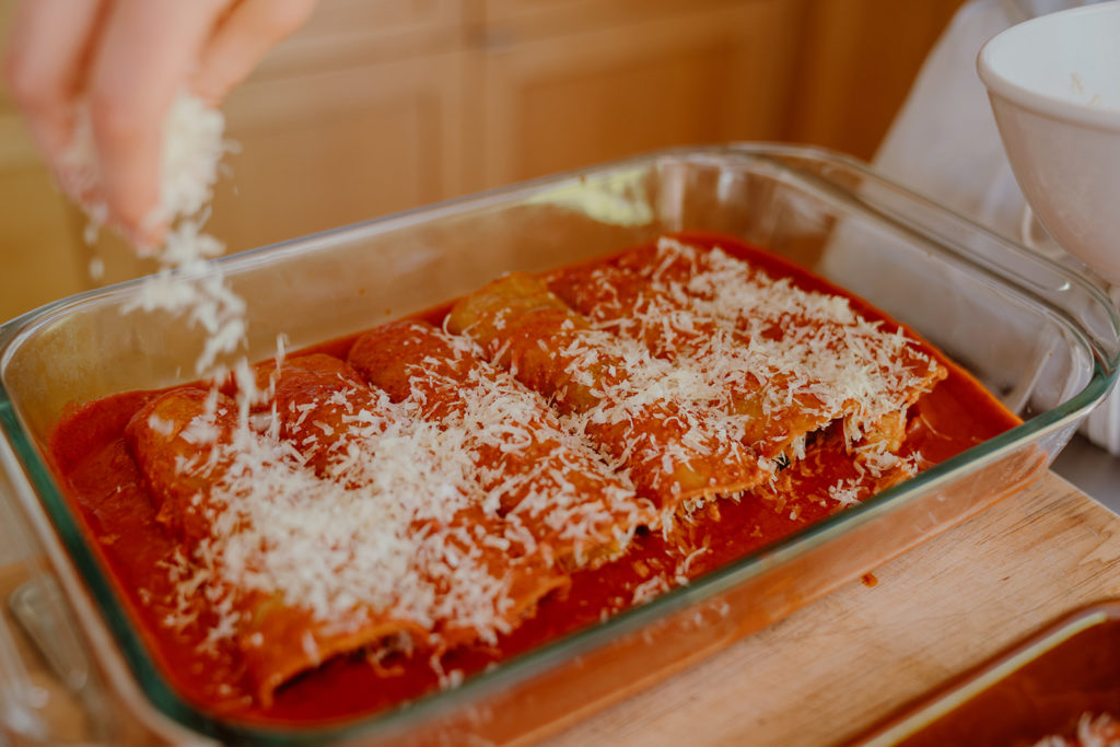 8 enchiladas in baking dish being topped with grated jack cheese.