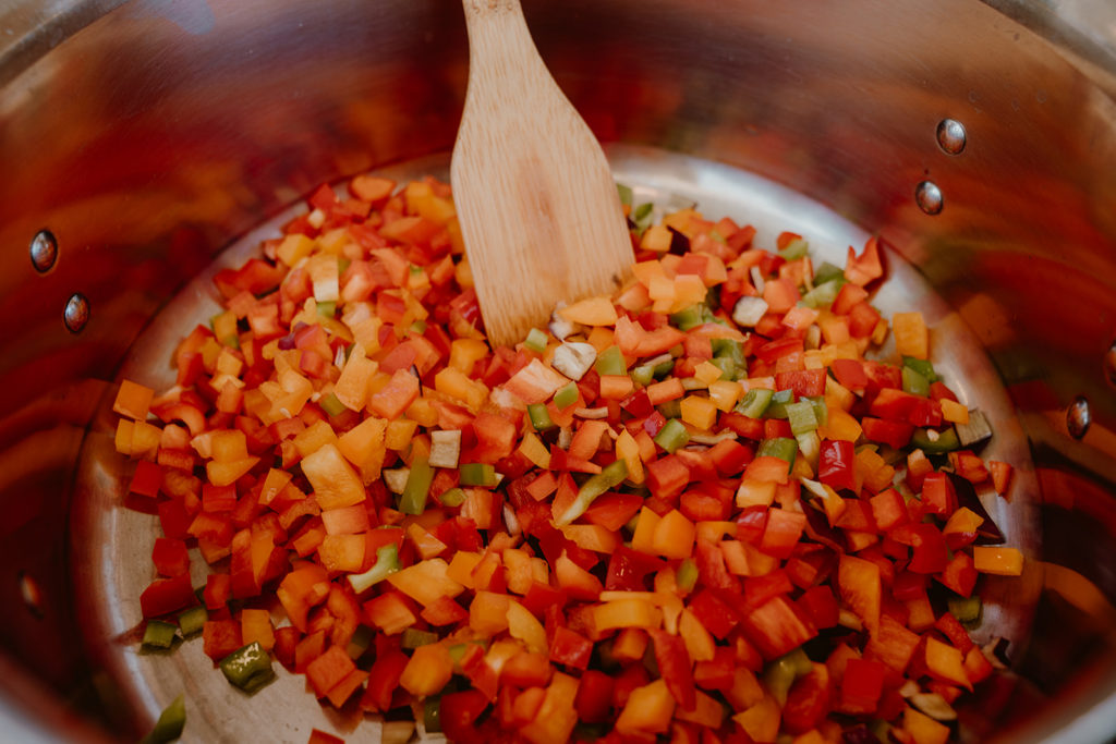Finely chopped sweet bell peppers, green bell pepper, and hot peppers in a pot.