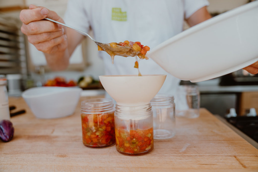 Hot pepper jelly being placed in jars for storage.