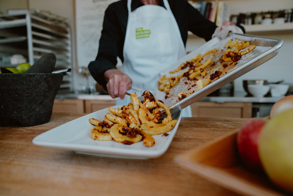 Roasted Delicata squash with Indian spices being transferred from baking sheet to platter.