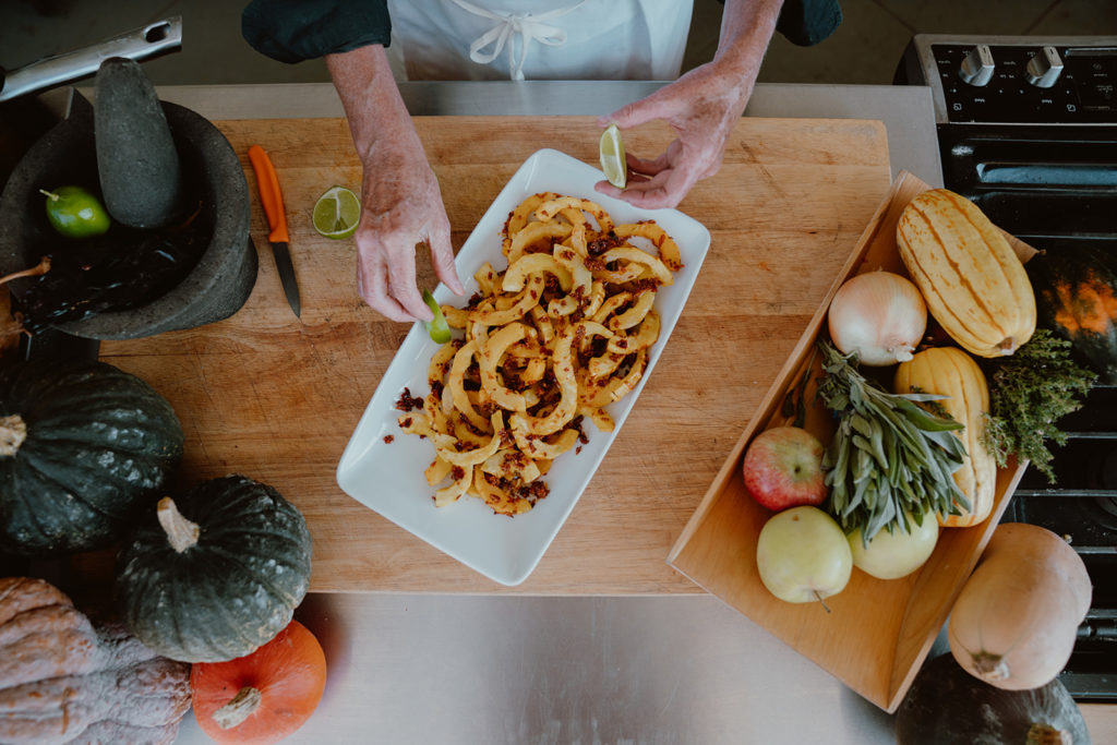 Hands placing lime slices next to roasted Delicata squash with Indian spices dish.