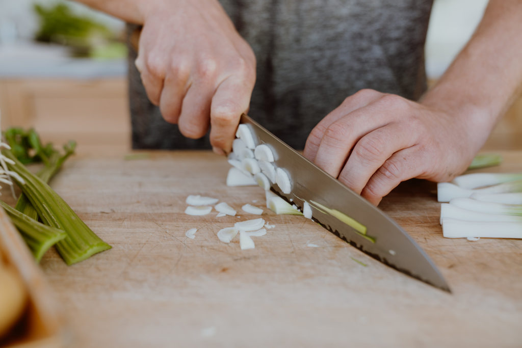 Cutting the bulb of green garlic into thin slices.