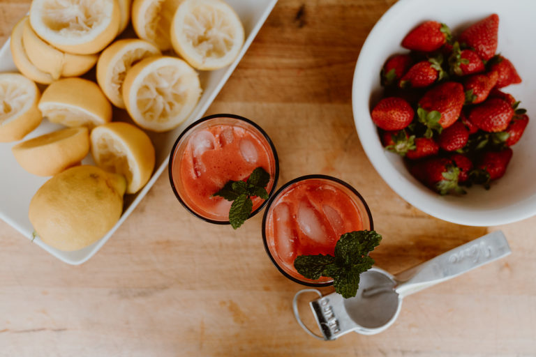 Two glasses of strawberry lemonade next to a bowl of strawberries and plate of lemons.