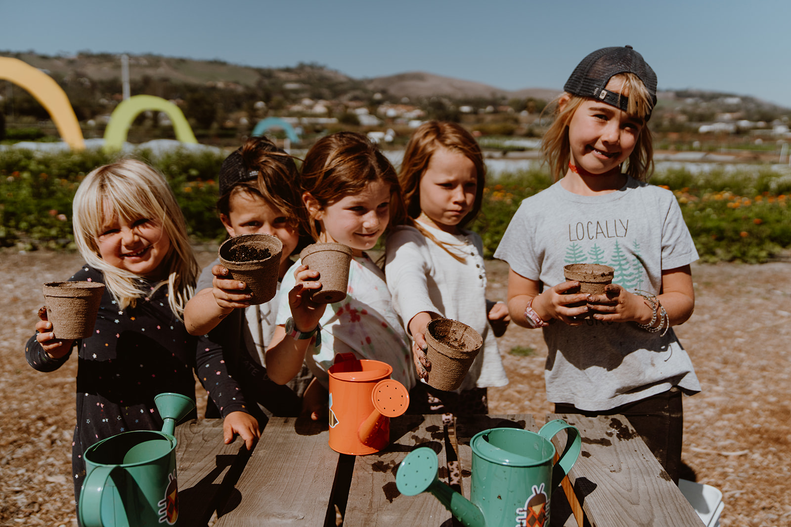 5 children stand at the end of a picnic table holding pots.