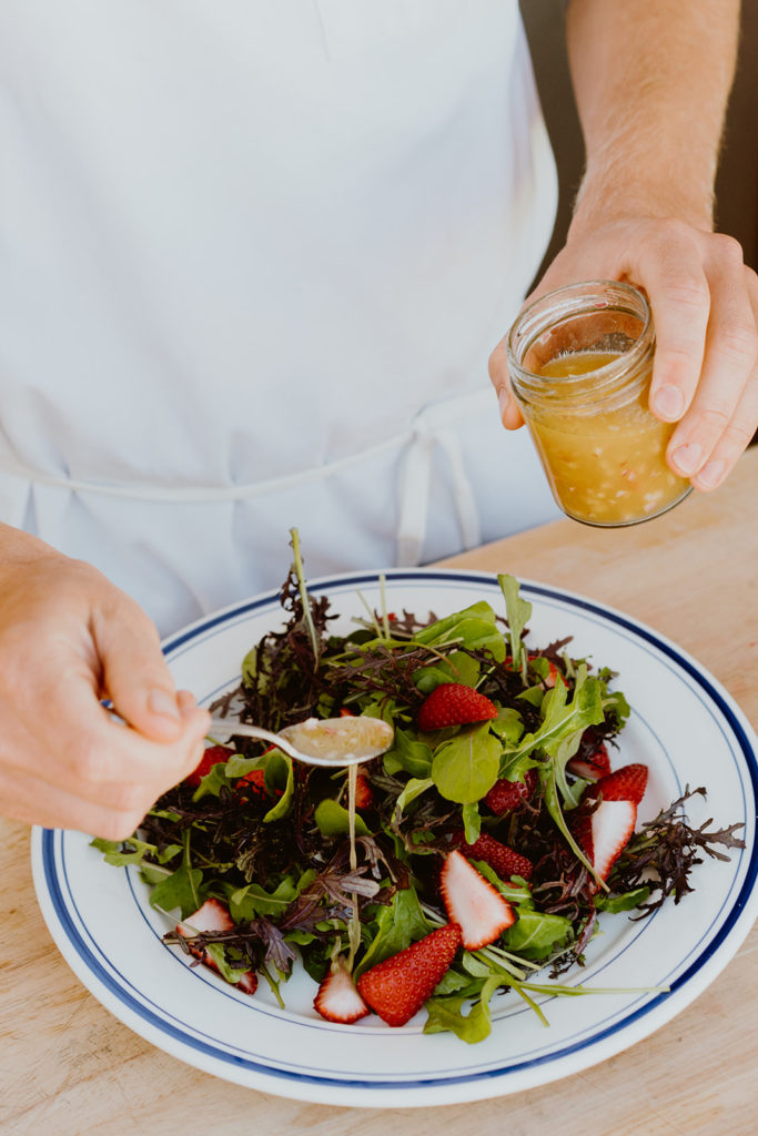 Adding dressing to salad in a shallow bowl.