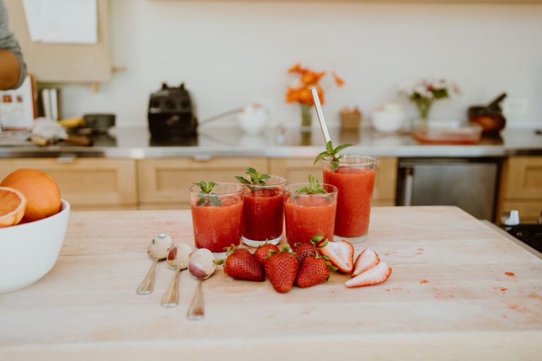 Strawberry & Blood Orange Granita on a wooden countertop in cups with spoons and whole strawberries.