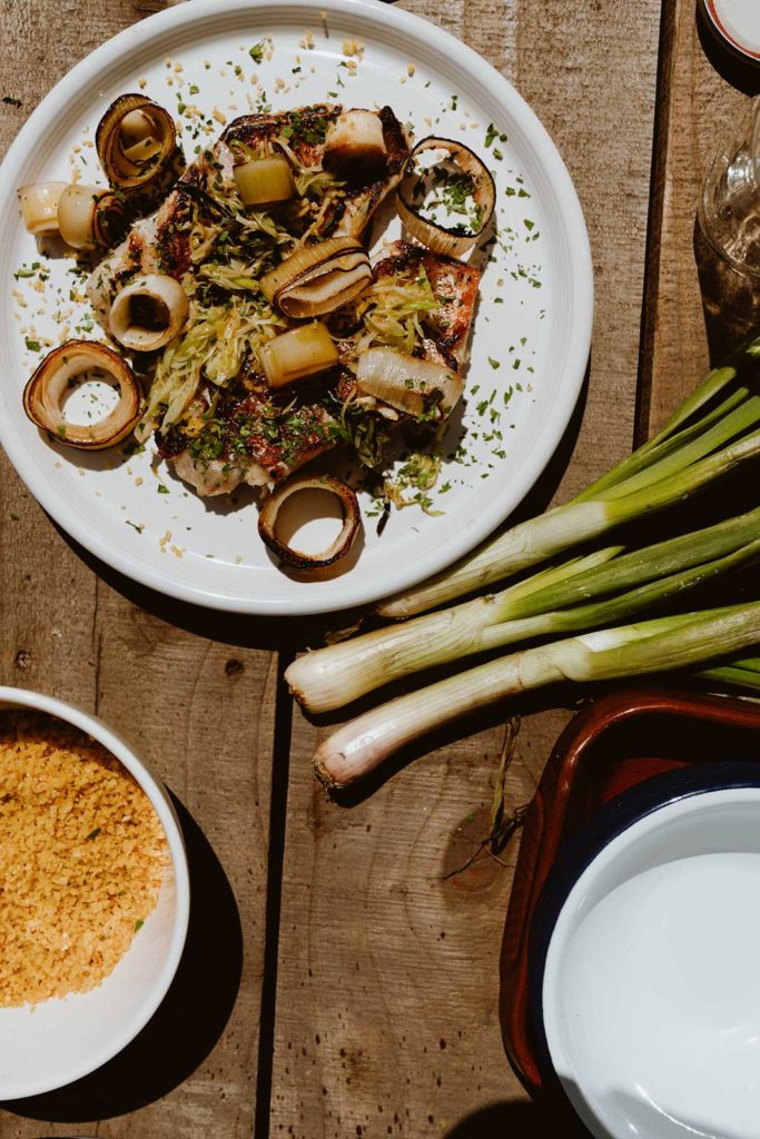 Green onions lay on a wooden table next to a plate of roasted onions and a bowl of rice.