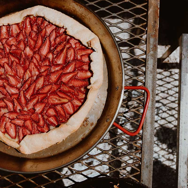 Strawberry tarte placed on a grill grate in a pan with a red handle.