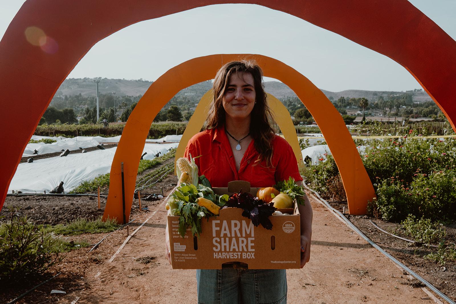Woman holding box of seasonal organic produce.