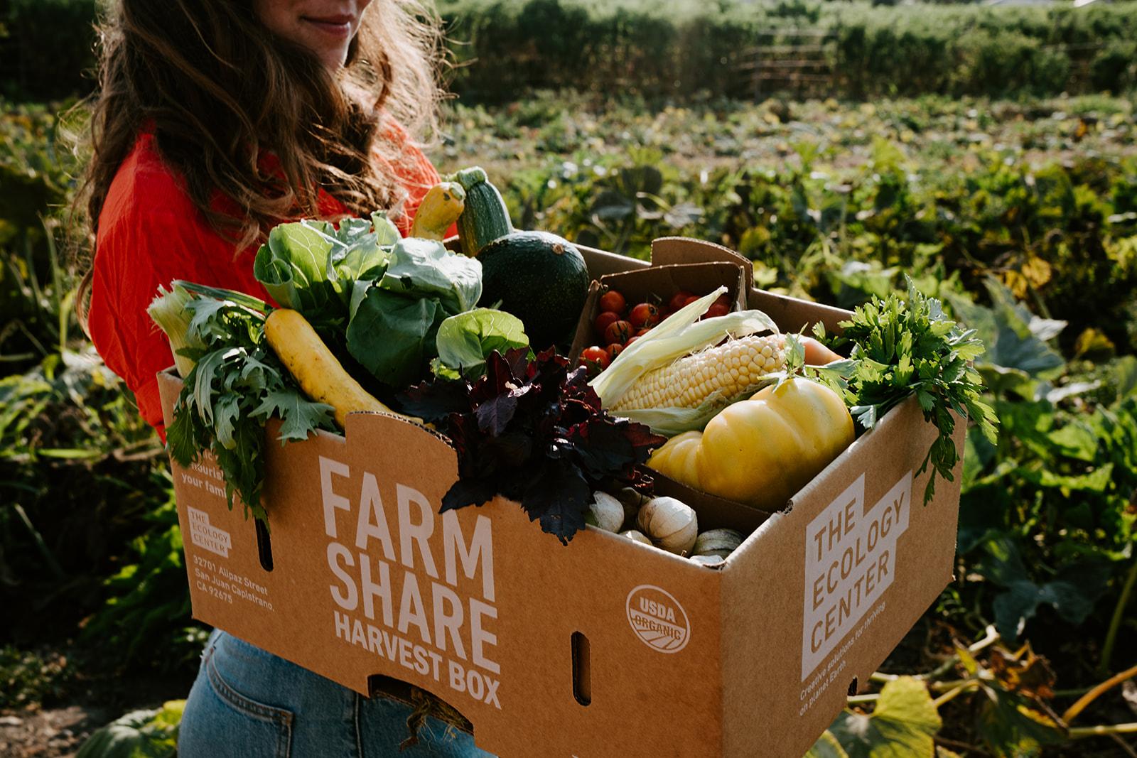 Woman holding her box of seasonal produce.