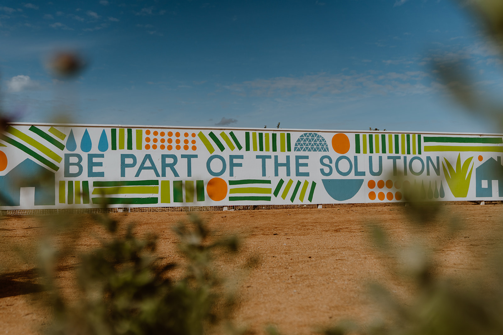 Be Part of The Solution phrase painted on fence.