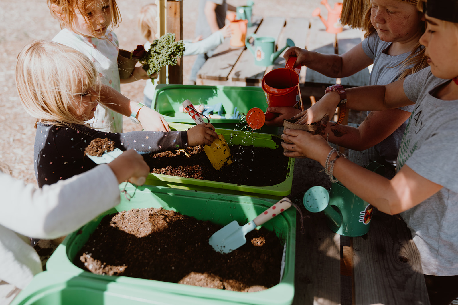 Children playing with garden tools and dirt.