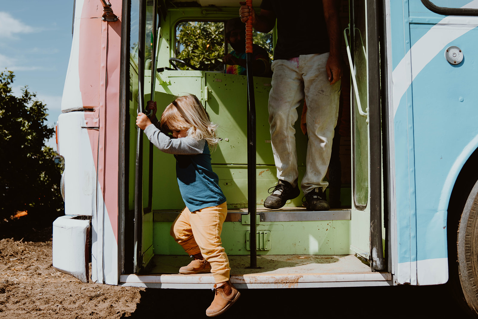 Child climbing down stairs of school bus.