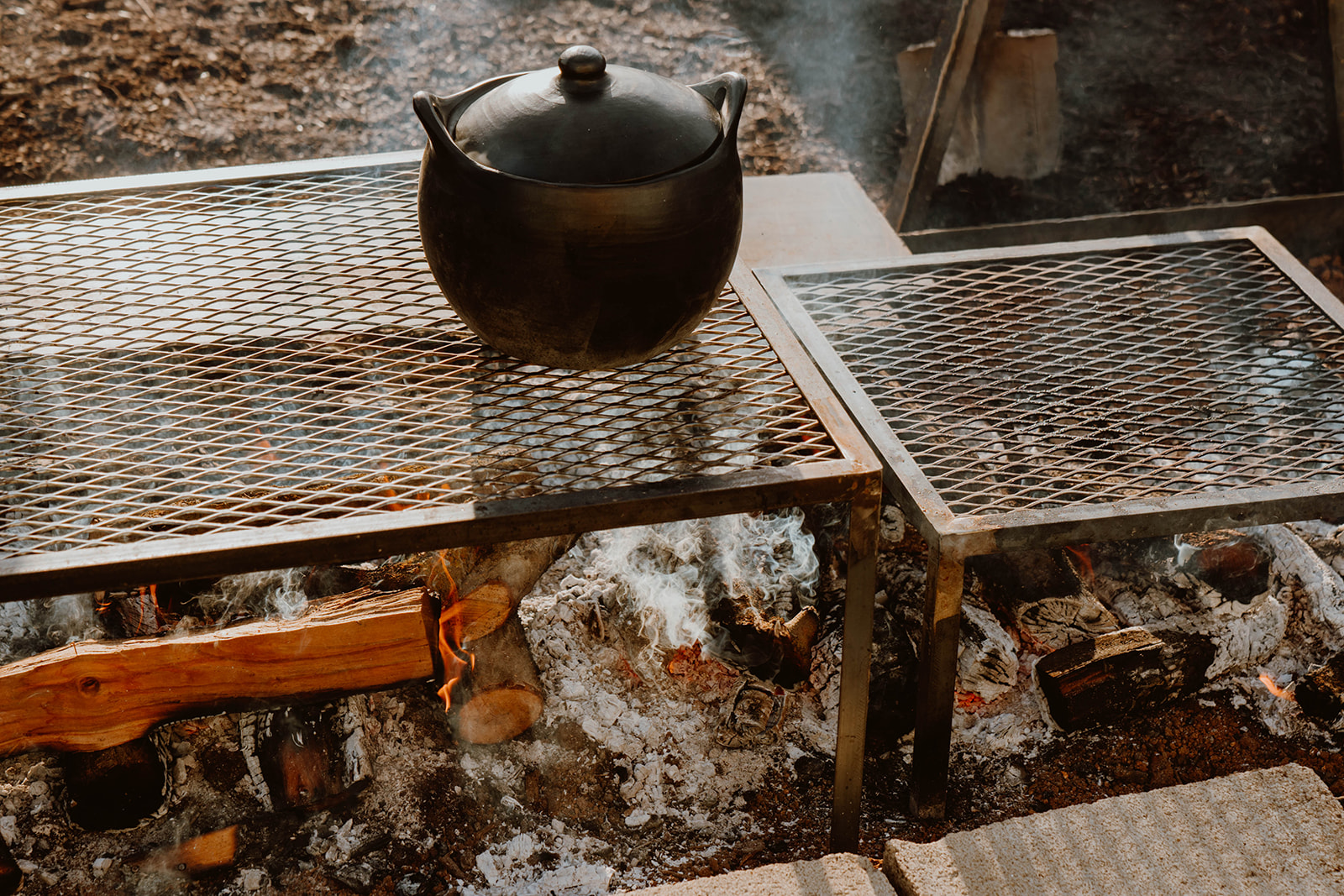 Pot rest on a grill grate over open woodfire.