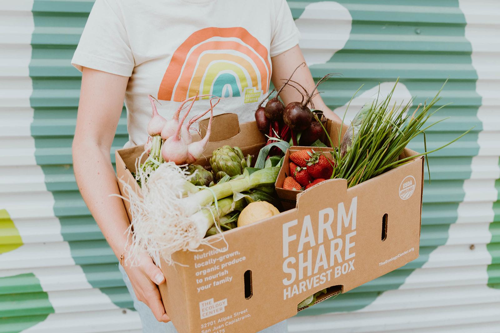 Woman holding box of fresh organic produce.
