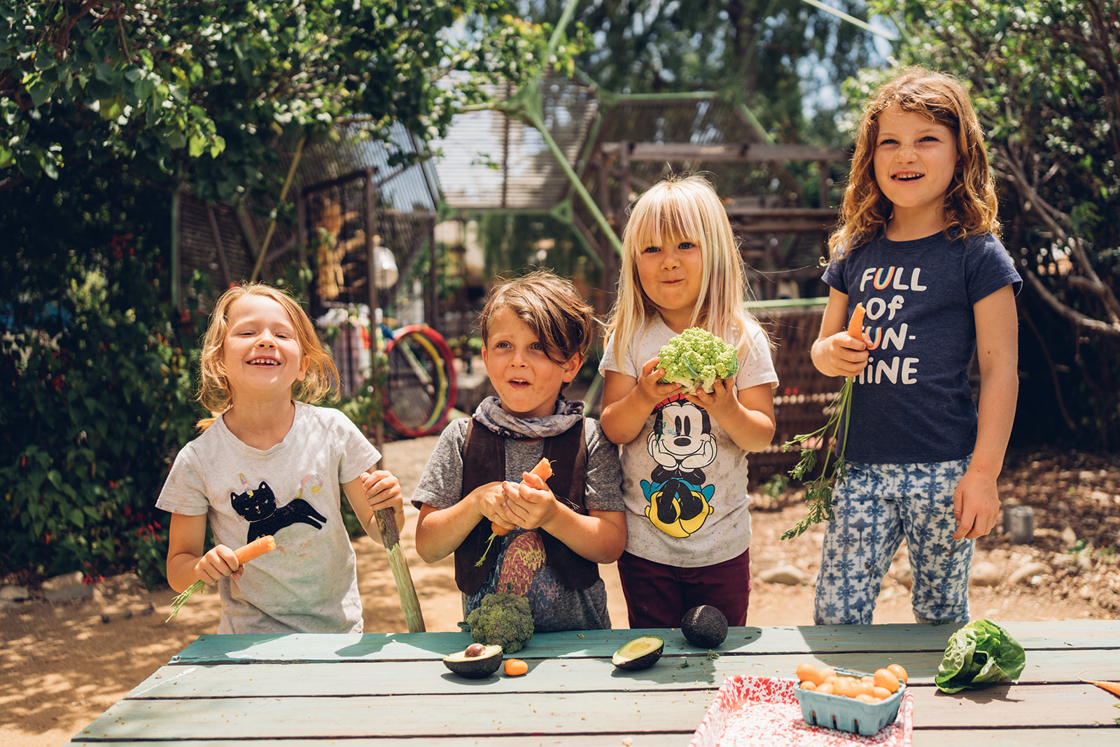 Group of young children sitting amongst harvested vegetables.
