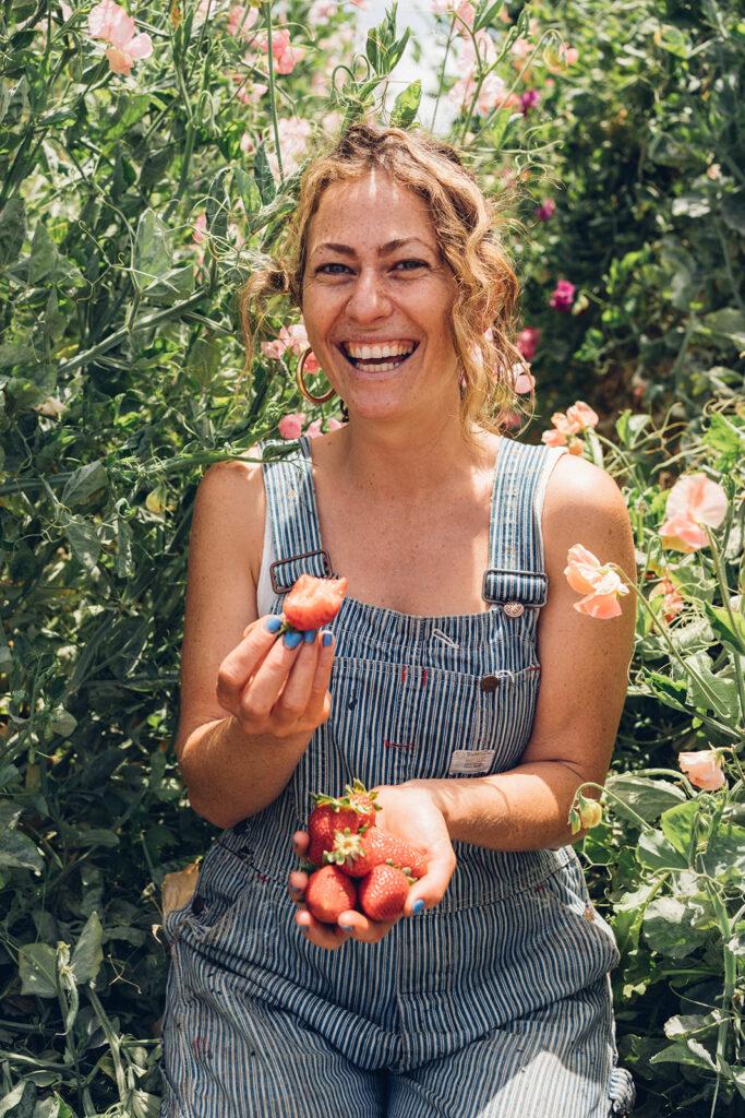 Happy person eats farm fresh strawberries in the field.