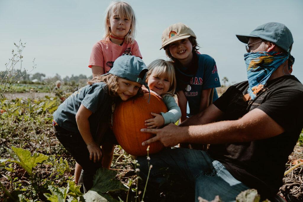 Children and teacher holding large pumpkin in farm field