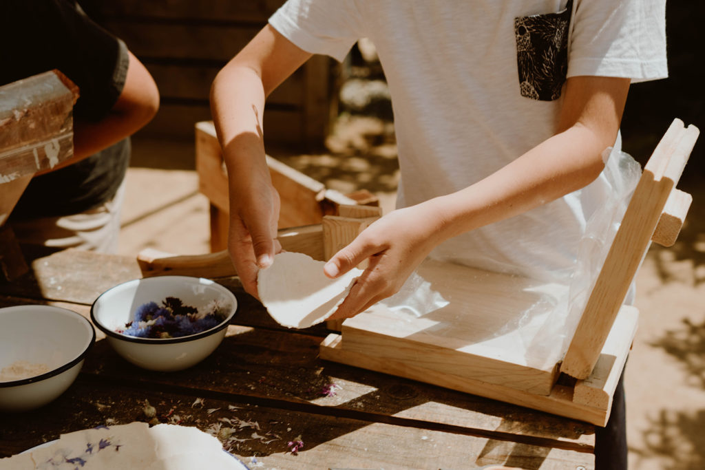 Child hand pressing corn tortilla