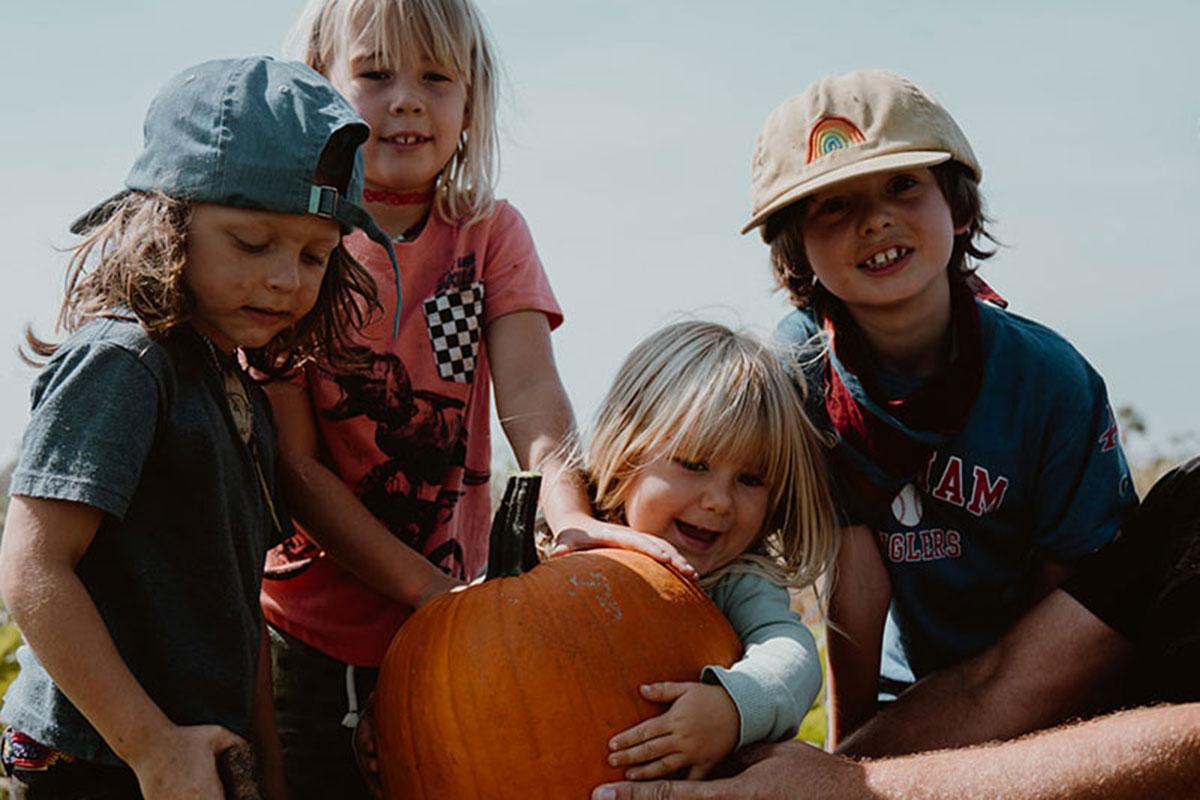 Children gathered around large pumpkin.