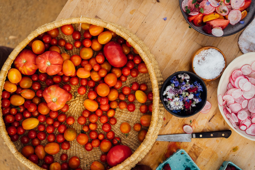 Top down photo of a variety of heirloom tomatoes and pickled radish on butcher block.