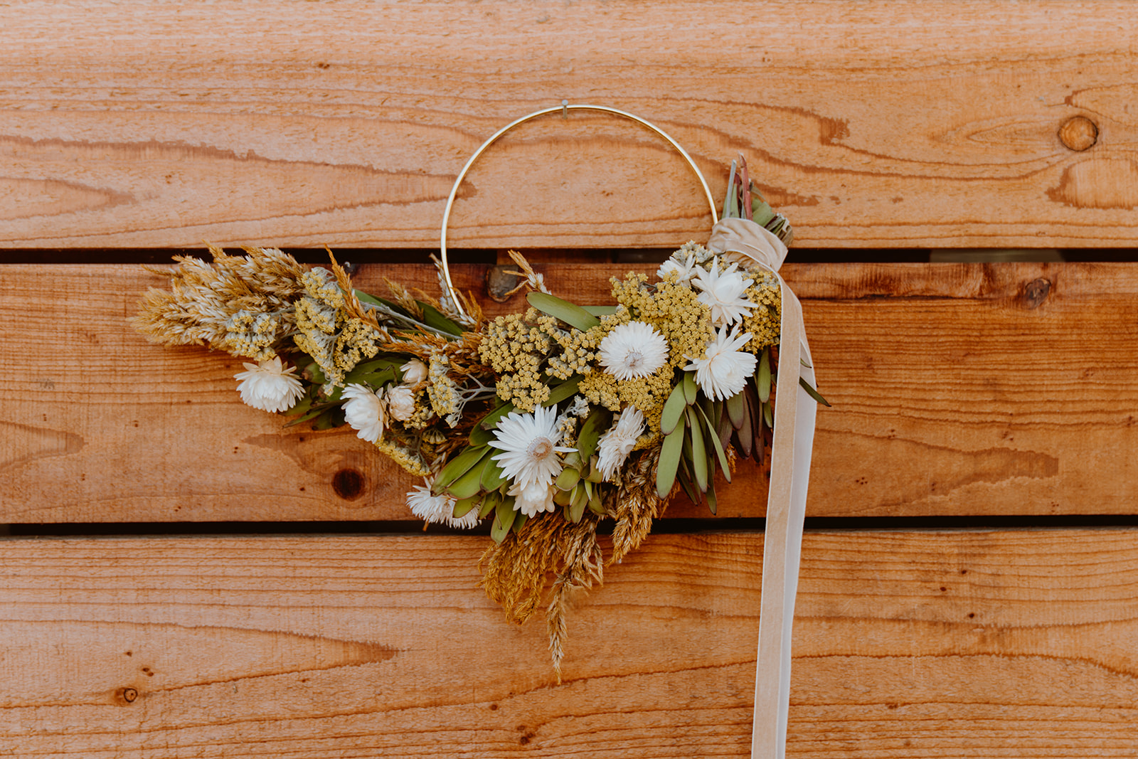 Wreath made up of dried flowers, leaves, branches and large ribbon.