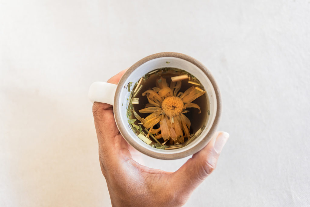 Hand holding mug of chamomile tea