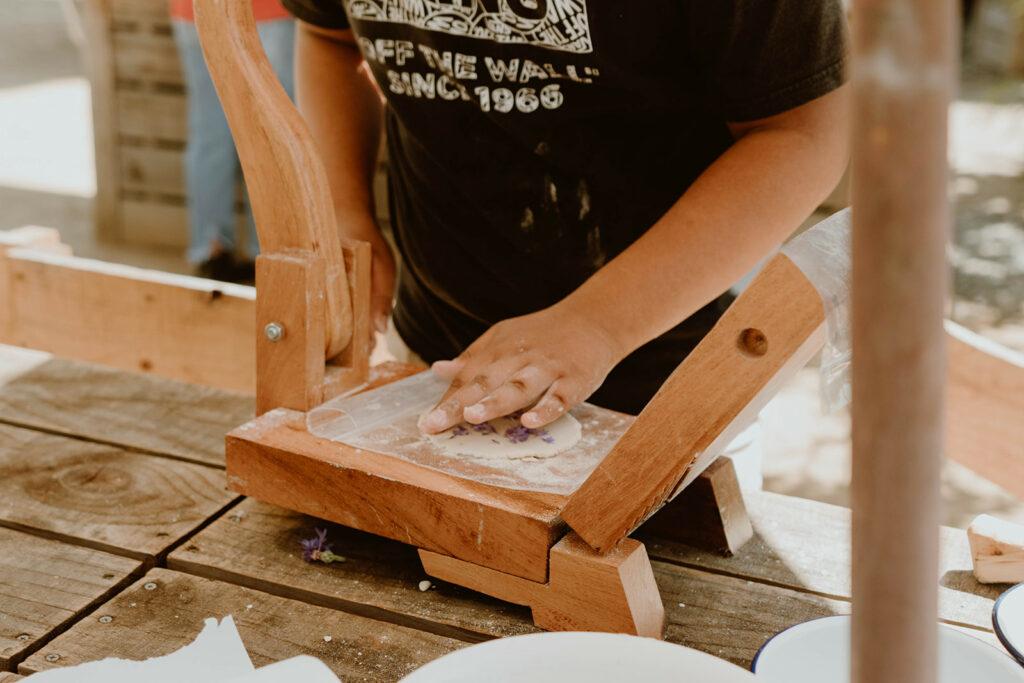 Child pressing tortilla on tortilla press.