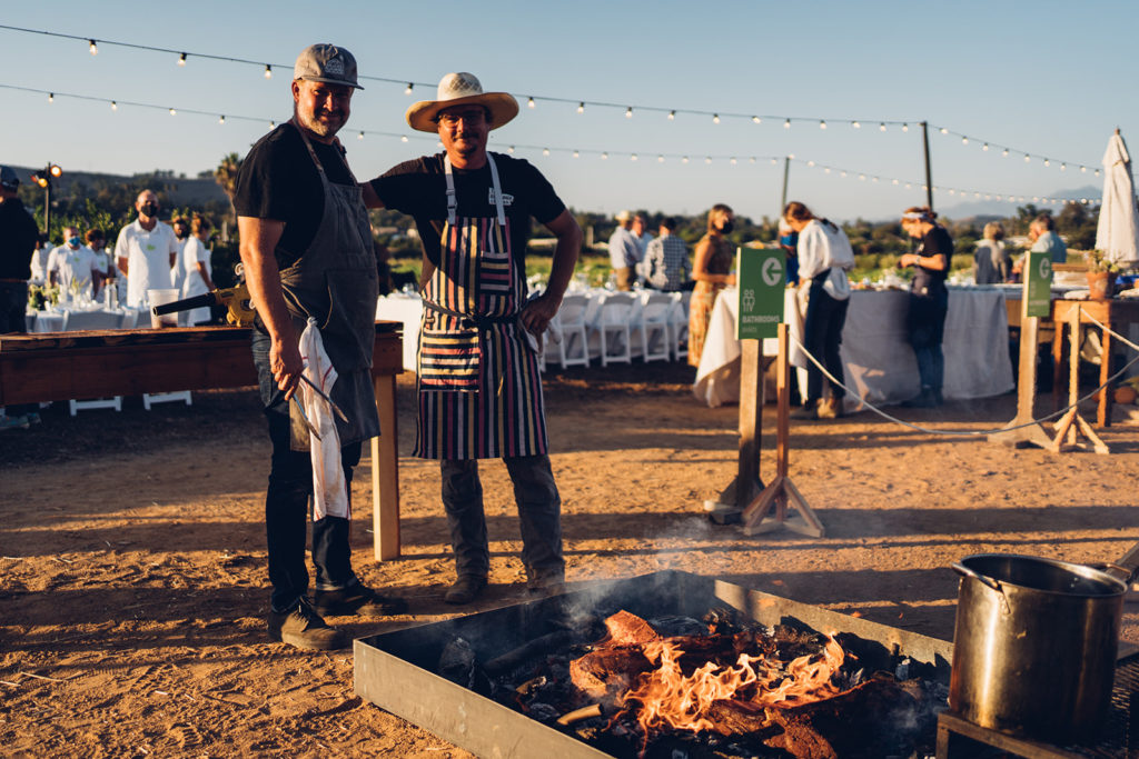 Chef Tim Byres and Glenn standing by open pit fire.