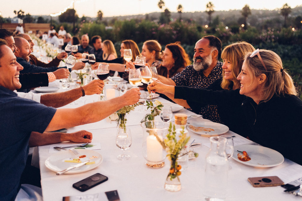 People seated at long dinner table raising glasses to cheers.